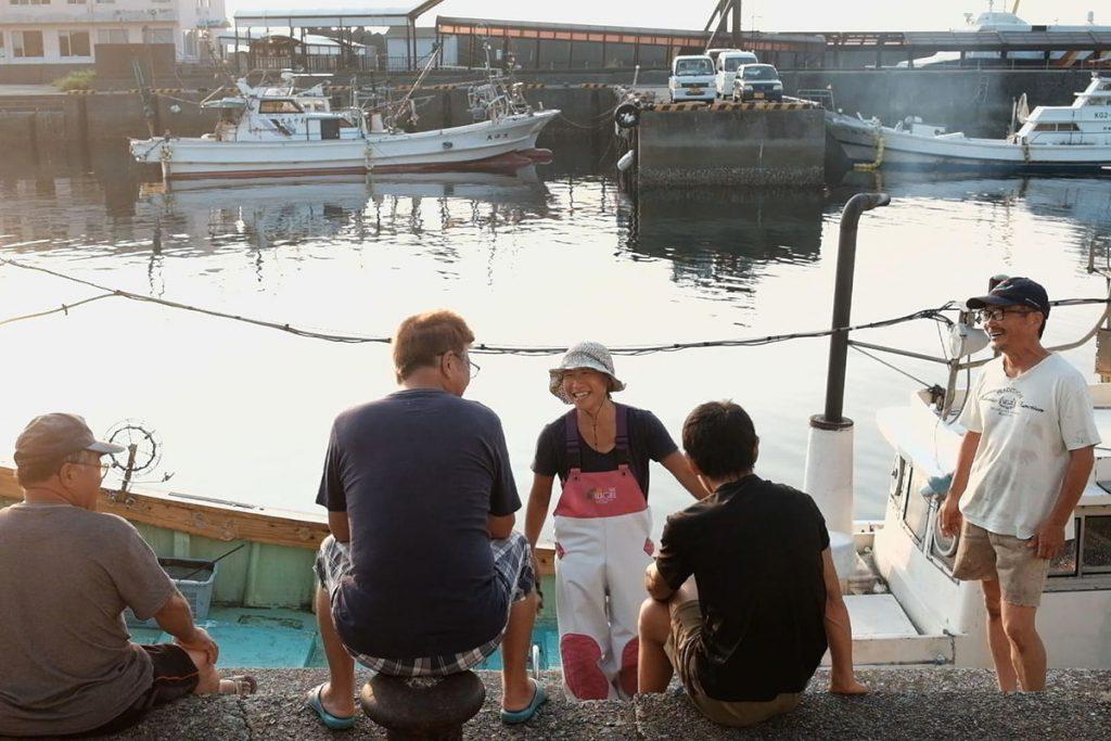 漁師が集い談笑する朝の安房漁港。島の人々はお互いをファーストネームで呼び合う