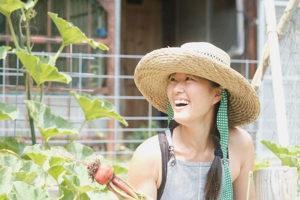 ファームで育てた野菜を嬉しそうに収穫する理恵さん