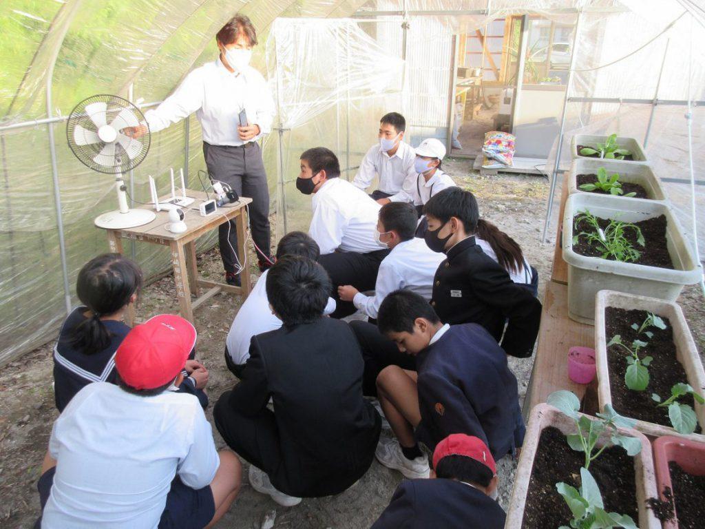 伊﨑田小学校のビニールハウスで機器のレクチャーをおこなう戸上さん