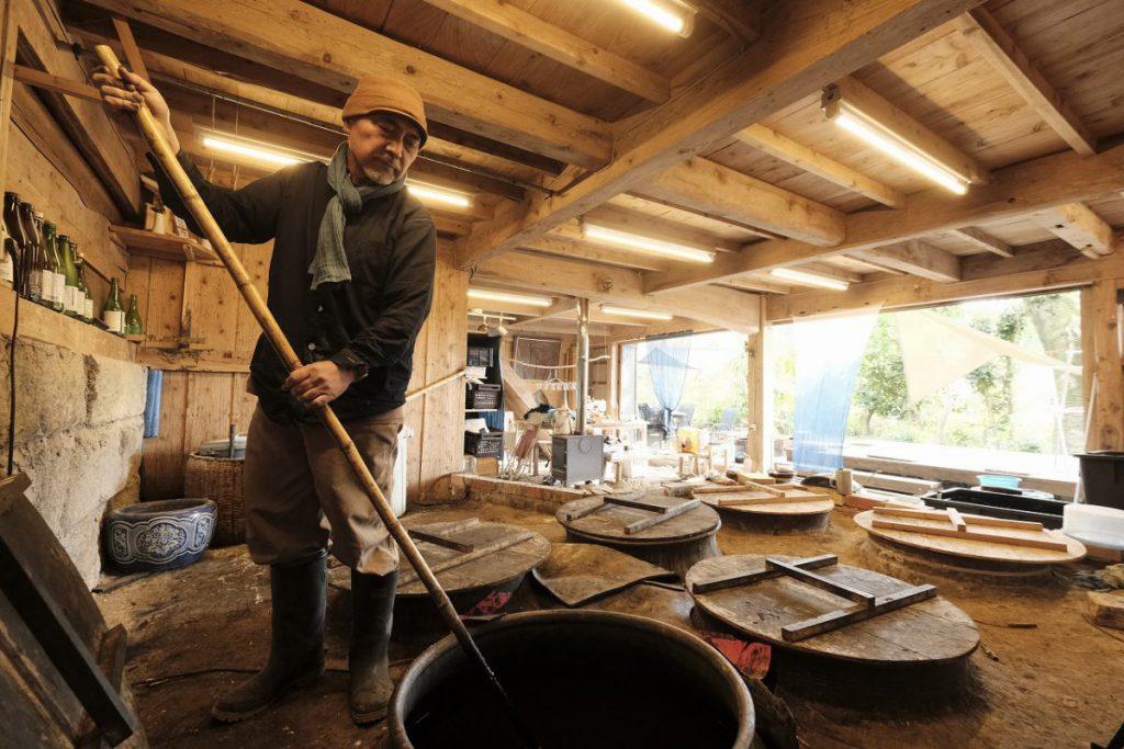 藍を仕込んだ甕壺に櫂を入れ撹拌させる神園さん